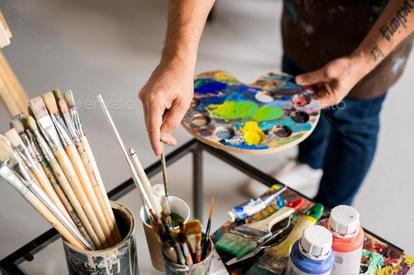Painter holding palette with mixed colors and putting paintbrush in water - Stock Photo - Images