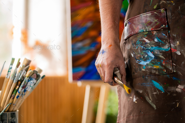 Hand of contemporary artist in apron holding paintbrush while working in studio - Stock Photo - Images