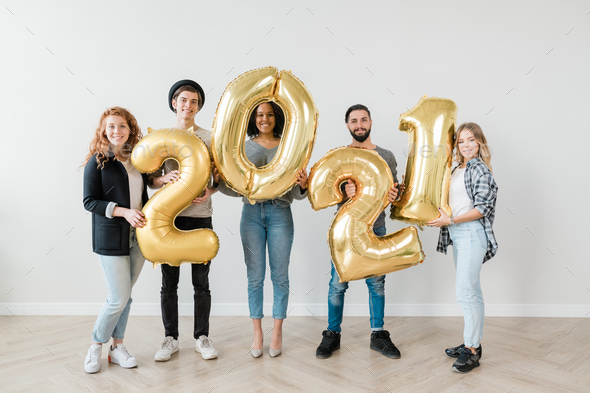 Multicultural group of young casual friends showing number of new year - Stock Photo - Images