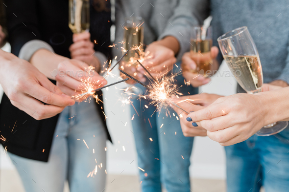 Hands of young friends holding burning bengal lights and flutes of champagne