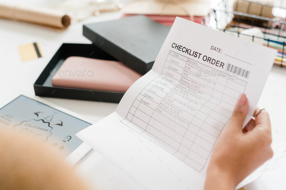 Paper with checklist order held by young female shopper looking through it - Stock Photo - Images