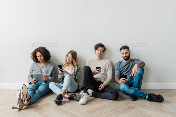 Intercultural milennials with smartphones sitting by white wall while texting - Stock Photo - Images