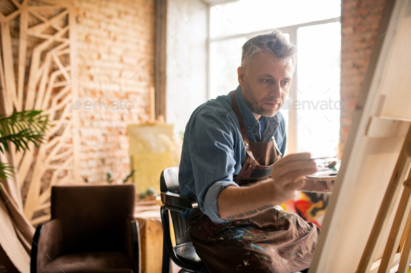 Professional painter in workwear sitting in front of unfinished painting - Stock Photo - Images
