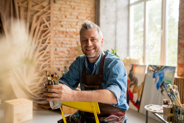 Cheerful artist in workwear sitting on chair in front of camera - Stock Photo - Images