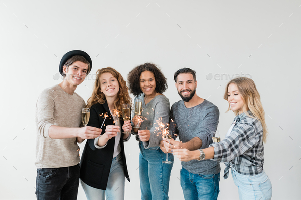 Cheerful friends toasting with flutes of champagne and holding bengal lights - Stock Photo - Images