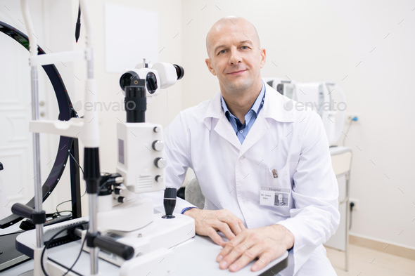 Happy bald mid-aged ophthalmologist in whitecoat sitting by workplace - Stock Photo - Images
