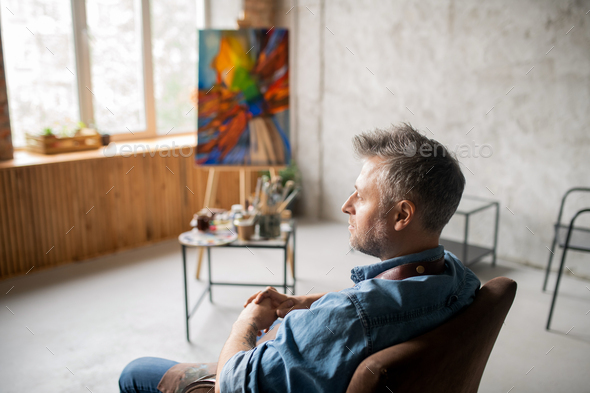 Middle aged pensive and restful painter in workwear sitting in armchair - Stock Photo - Images