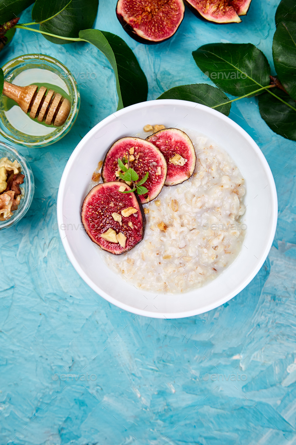 A bowl of porridge with figs slices and walnuts - Stock Photo - Images