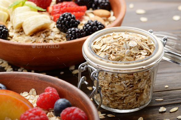 Glass gar with oats with bowl of muesli and berries aside closeu - Stock Photo - Images