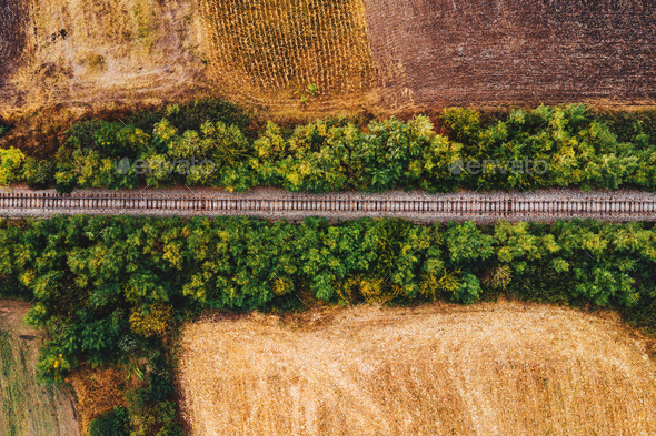 Old railroad track through countryside in autumn, aerial view - Stock Photo - Images