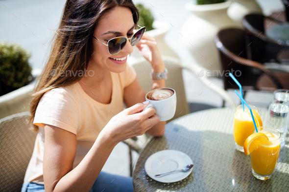 Young pretty woman drinking cappuccino, coffee in cafe outdoors - Stock Photo - Images