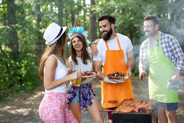 Group of happy young friends having barbecue party, outdoors - Stock Photo - Images