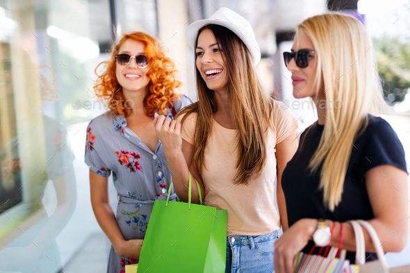 Happiness, friends, shopping and fun concept-smiling young women with shopping bags - Stock Photo - Images