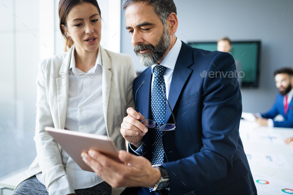 Happy business colleagues in modern office using tablet - Stock Photo - Images