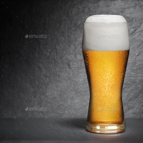 Pint of fresh beer with foam on black background - Stock Photo - Images