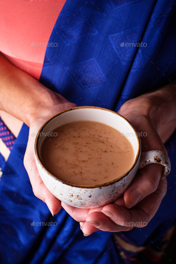 Woman  holding a cup of masala  tea - Stock Photo - Images