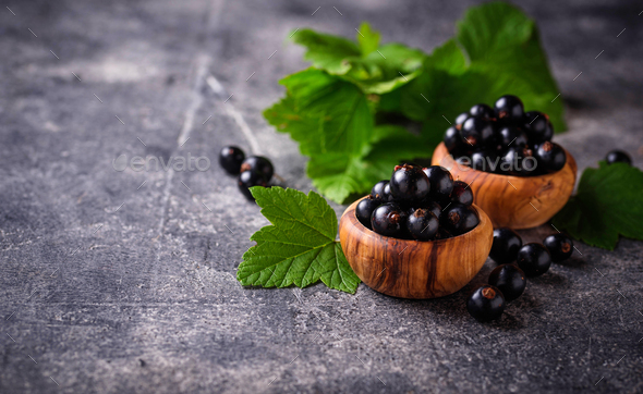 Black currant with leaves in wooden bowls - Stock Photo - Images