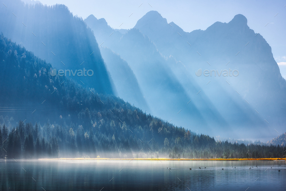Majestic mountains in bright sunbeams and foggy lake at sunrise - Stock Photo - Images