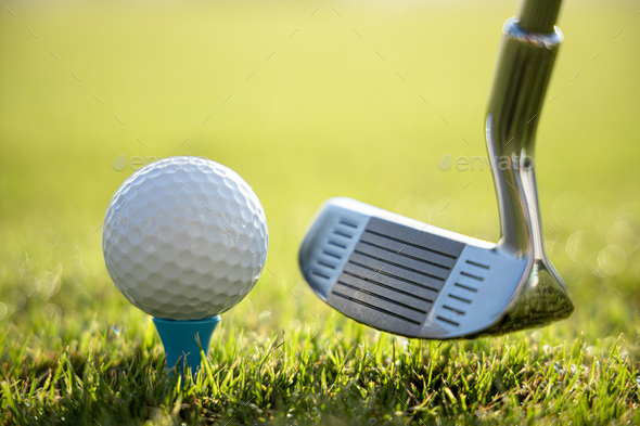 Golf ball on tee in front of driver - Stock Photo - Images
