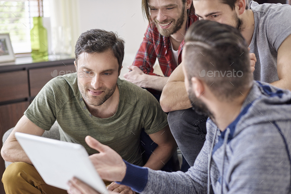 Man presenting to friends his new tablet - Stock Photo - Images