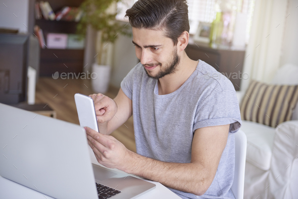 Man sitting in front of his desk and using a smartphone - Stock Photo - Images