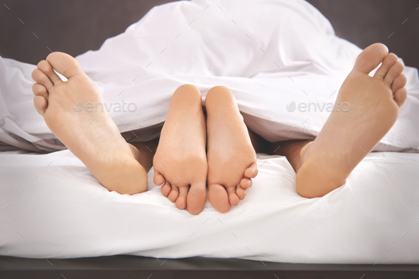Bare human feet sticking out from the bed - Stock Photo - Images