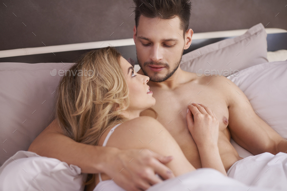 Beautiful couple lying down in the bed - Stock Photo - Images