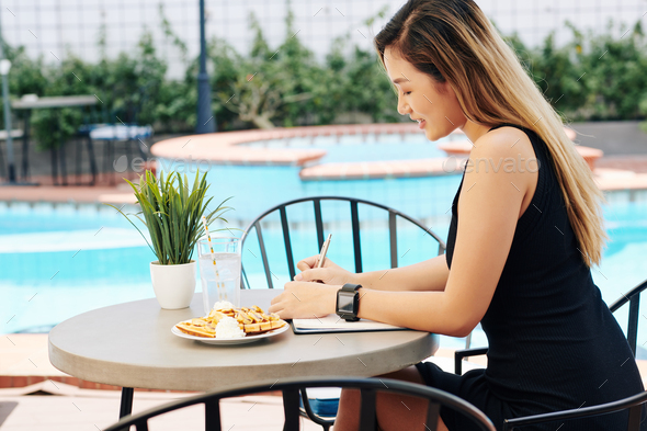 Woman eating breakfast and filling journal - Stock Photo - Images