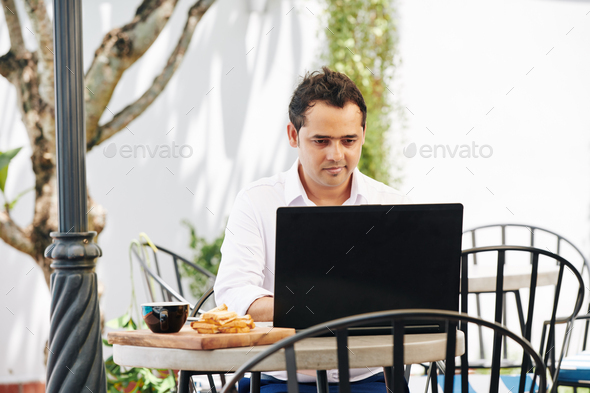 Indian man working on laptop in cafe - Stock Photo - Images