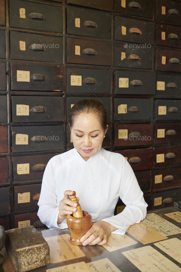 Asian woman working at tradional pharmacy - Stock Photo - Images