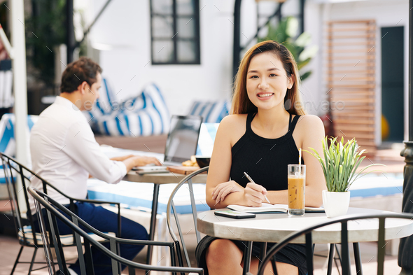 Beautiful businesswoman at cafe table - Stock Photo - Images