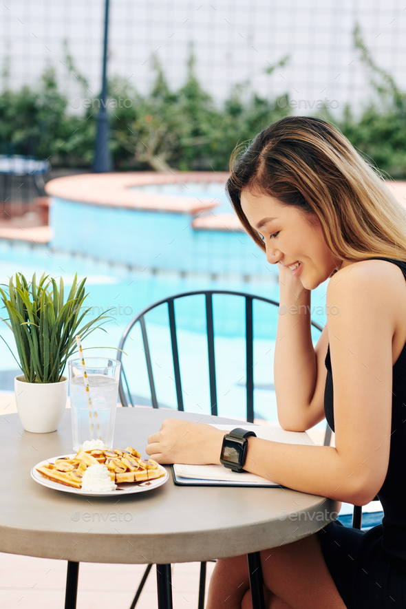 Smiling woman eating waffles and reading a book - Stock Photo - Images