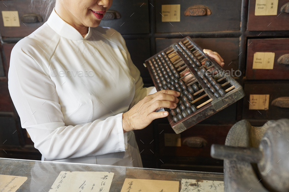 Woman working at old traditional pharmacy - Stock Photo - Images