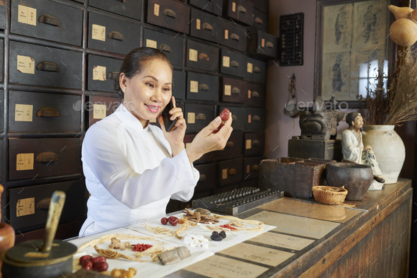 Smiling female pharmacy worker looking at big dry berry in her hand - Stock Photo - Images
