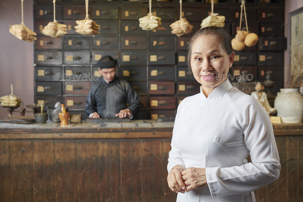 Aged woman at traditional Asian pharmacy - Stock Photo - Images