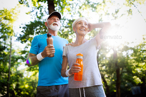 Mature or senior couple doing sport outdoors, jogging in a park - Stock Photo - Images
