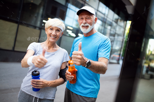 City running couple jogging outside. Senior couple runners training outdoors - Stock Photo - Images