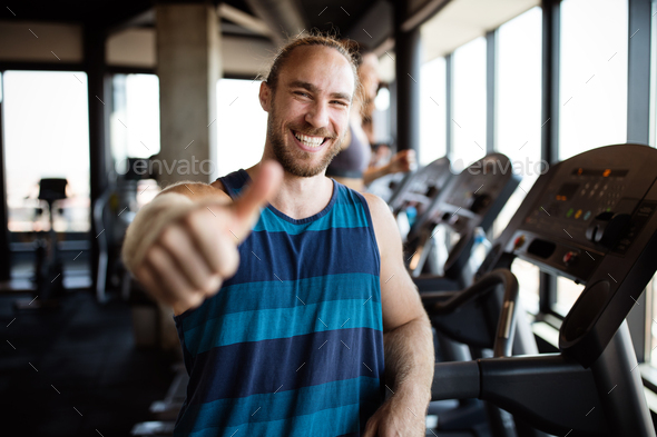 Portrait of happy man gesturing thumbs up at gym - Stock Photo - Images