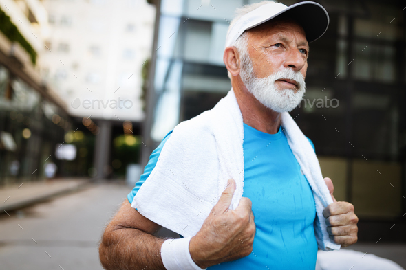 Attractive retired man with a nice smile jogging in park - Stock Photo - Images