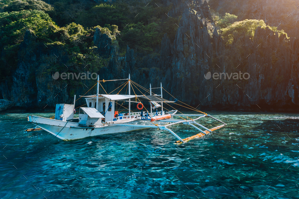Banca local boat on turquoise water against huge limestone cliffs. Island hopping tour trip - Stock Photo - Images
