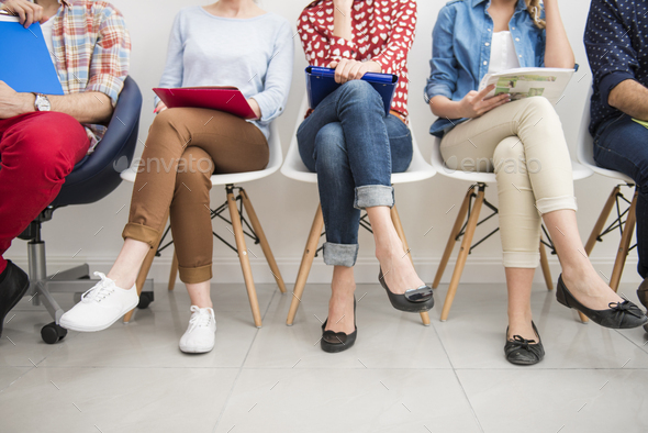 People sitting in the raw at the passage - Stock Photo - Images