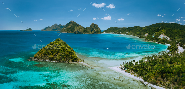 Palawan, Philippines. Las Cabanas beach with rocky mountains and village El Nido in background - Stock Photo - Images