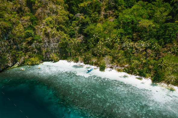 Aerial drone view of a secluded deserted tropical beach with lonely tourist boat surrounded by - Stock Photo - Images