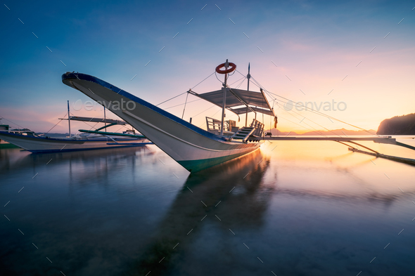 El Nido, Palawan, Philippines. Traditional banca boat in the beach bay in golden sunset light - Stock Photo - Images