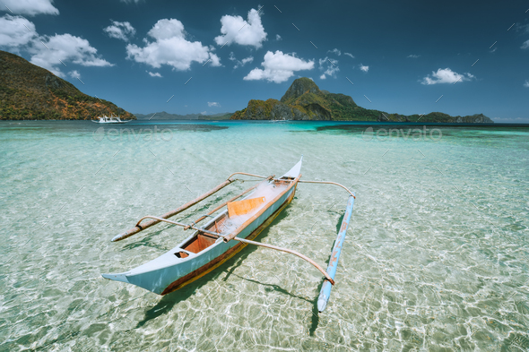 Palawan, Philippines. Traditional small fishing banca boat in front of Cadlao Island in crystal - Stock Photo - Images