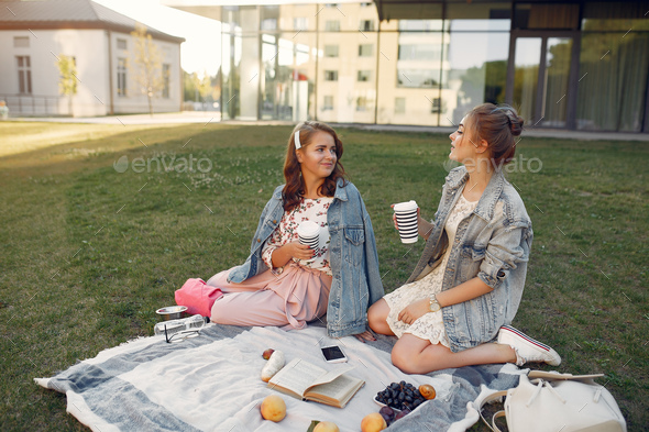 Girls sitting on a blanket in a summer park - Stock Photo - Images