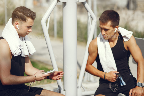 Handsome men in a sports clothes sitting near simulators - Stock Photo - Images