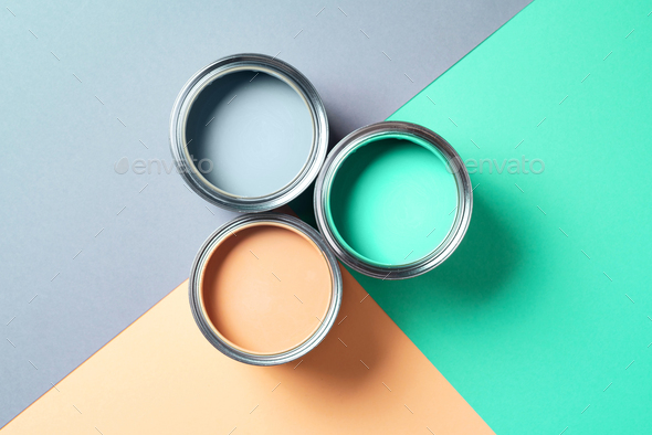 Open cans of paint on bright multicolored background. Top view. Copy space. Trendy green color - Stock Photo - Images