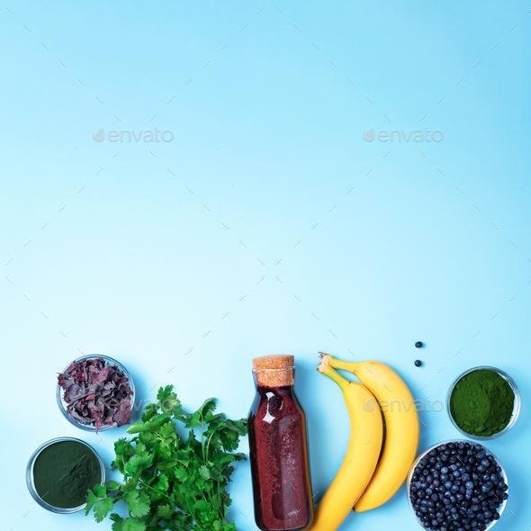 Blueberries, bilberry, barley grass, spirulina, orange juice, dulse, cilantro on blue background - Stock Photo - Images