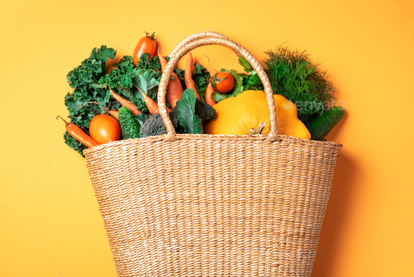 Straw basket with organic vegetables over trendy yellow background. Healthy food, vegetarian diet - Stock Photo - Images